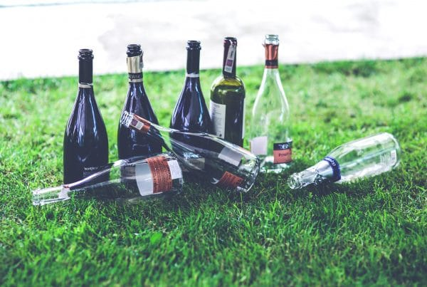 5 Signs You Have a Problem with Alcohol - A bottle of wine sitting on top of a grass covered field - Drinking